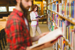 Hipster student picking a book in library. At the university Royalty Free Stock Photography