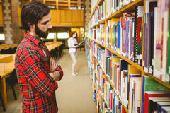Hipster student picking a book in library. At the university Royalty Free Stock Image