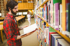 Hipster student picking a book in library. At the university Royalty Free Stock Photos