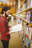 Hipster student picking a book in library. At the university Stock Image