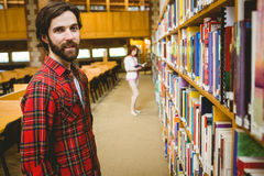 Hipster student picking a book in library. At the university Stock Photos
