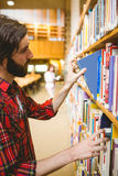 Hipster student picking a book in library. At the university Royalty Free Stock Images