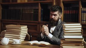 Hipster student studying in library. Research and studying concept. Man in classic suit, professor with concentrated stock footage