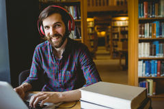 Hipster student studying in library Stock Image
