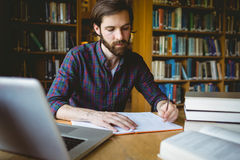 Hipster student studying in library Royalty Free Stock Photography