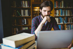 Hipster student studying in library Royalty Free Stock Images