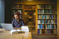 Hipster student studying in library Royalty Free Stock Photos