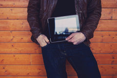 Hipster student with touch pad standing on wooden background Stock Image