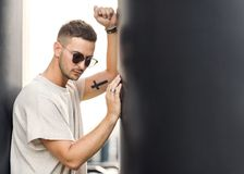 Hipster style guy. Fashion man standing near black wall Royalty Free Stock Image