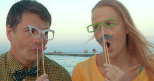 Hipster style people making funny faces outdoor. Young man and woman with hipster style paper glasses and moustache having fun while making goofy faces outdoor stock video