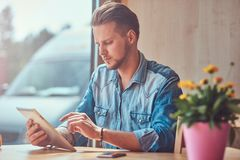 Hipster with a stylish haircut and beard sits at a table in a roadside cafe, looks something in the tablet. Handsome hipster with a stylish haircut and beard Royalty Free Stock Image