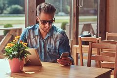 Hipster with a stylish haircut and beard sits at a table in a roadside cafe, looks something in the tablet. Handsome hipster with a stylish haircut and beard Stock Image