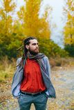 Hipster. A stylish man with dreadlocks and beard in a red shirt and grey jacket. Groom posing on nature. Autumn wedding royalty free stock photos