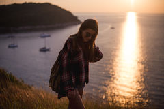 Hipster stylish woman traveler looking on a sea or ocean at the sunset Royalty Free Stock Images