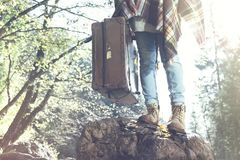 Hipster with suitcase travels in the mountains stock image