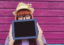 Hipster with tablet and hat with pink wood background. Digital composite of hipster with tablet and hat with pink wood background Royalty Free Stock Photos