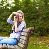 Hipster taking photo with retro photo camera sitting on be Royalty Free Stock Images