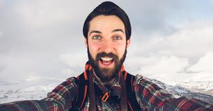 Hipster taking selfie while standing on mountain against sky Stock Images