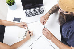 Hipster is talking to his colleague at workplace Royalty Free Stock Photography