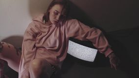 Hipster tattooed girl sitting near working static tv set in dark room. Hipster tattooed caucasian girl with glitter on face in pink hoodie and black cap sitting stock video