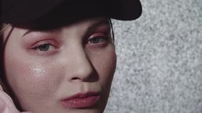 Hipster tattooed woman face in front of working static tv set in dark room. Hipster tattooed caucasian woman with glitter on face in pink hoodie and black cap stock video footage