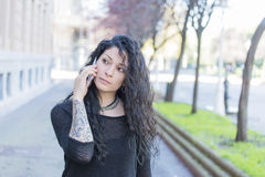 Hipster tattooed woman talking by smart phone in the street. Royalty Free Stock Image