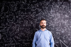 Hipster teacher against big blackboard with mathematical symbols Royalty Free Stock Photos