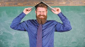 Hipster teacher aggressive with laptop as roof goes mad about teaching. Teacher bearded man with modern laptop. Chalkboard background. Can not get used to royalty free stock image