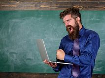 Hipster teacher aggressive with laptop goes mad about slow speed internet connection. Teacher bearded man modern laptop. Chalkboard background. Slowly internet stock images