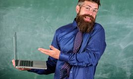 Hipster teacher confused expression holds laptop. Distance education issues. Teaching issues using modern technologies stock photography