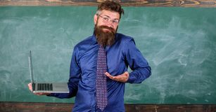 Hipster teacher confused expression holds laptop. Teaching issues using modern technologies. Teacher bearded man royalty free stock photos