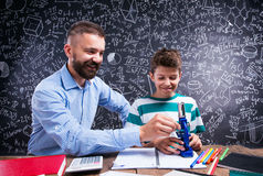 Hipster teacher with his student with microscope, big blackboard. Hipster teacher with his student sitting at the desk with microscope and other school supplies Royalty Free Stock Photos