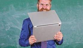 Hipster teacher wear eyeglasses and necktie bites laptop. Man hungry for knowledge. He needs new information. Thirst of. Knowledge. Teacher bearded man bites royalty free stock photography