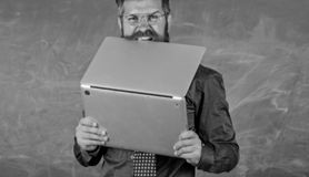 Hipster teacher wear eyeglasses and necktie bites laptop. Man hungry for knowledge. He needs new information. Thirst of. Knowledge. Teacher bearded man bites stock image
