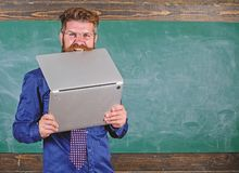 Hipster teacher wear eyeglasses and necktie bites laptop. Man hungry for knowledge. Teacher bearded man bites modern. Laptop chalkboard background. He needs new royalty free stock photo