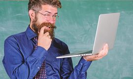Hipster teacher wear eyeglasses and necktie holds laptop surfing internet. Teacher bearded cunning man modern laptop. Surfing internet chalkboard background stock image