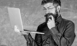 Hipster teacher wear eyeglasses and necktie holds laptop surfing internet. Teacher bearded cunning man modern laptop. Surfing internet chalkboard background stock photography