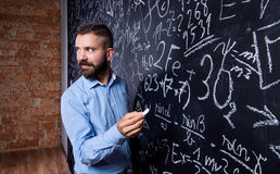 Hipster teacher writing on big blackboard with mathematical symbols. And formulas. Studio shot on black background stock image