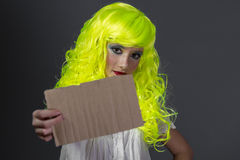 Hipster, teenager with fluorescent yellow wig, carrying a cardbo Royalty Free Stock Photo