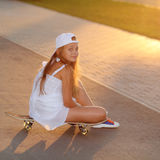 Hipster teenager with skateboard Stock Images