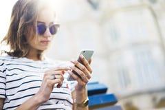 Hipster texting bericht op smartphone of technologie, model van het lege scherm Meisje die cellphone bij de bouw van kasteelachte stock afbeelding