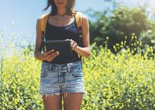 Hipster texting message on tablet or technology, mock up of blank screen. Girl using computer on yellow flowers background close royalty free stock photo