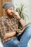 Hipster thoughtfully reading a book on  tablet. Handsome red-haired hipster thoughtfully reading a book on  tablet Royalty Free Stock Photos
