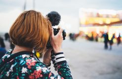 Hipster tourist girl hold in hands modern photo camera, take photography click on defocus background bokeh light in evening street royalty free stock photo