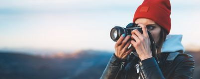 Hipster tourist girl hold in hands take photography click on modern photo camera, photographer look on camera technology, journey royalty free stock image