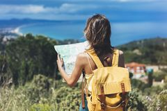 Hipster tourist hold and look map on trip, lifestyle concept adventure, traveler with backpack on background mountain and blue sea stock images