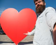 Hipster, tourist with long beard looking at camera, taking selfie photo. Love symbol concept. Man, with beard on. Cheerful face pointing at red heart sculpture Royalty Free Stock Photography
