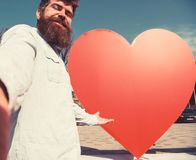 Hipster, tourist with long beard looking at camera, taking selfie photo. Love symbol concept. Man, with beard on. Cheerful face pointing at red heart sculpture stock photo