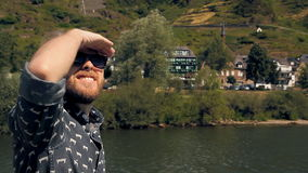 Hipster tourist is sailing on a ship. Young bearded hipster in sunglasses is sailing on a ship. The river is in Europe, there are beautiful buildings in the stock footage