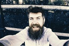 Hipster, tourist with tousled hair and long beard looking at camera, taking selfie photo. Vlogging concept. Man, tourist. With beard and mustache on cheerful royalty free stock photography